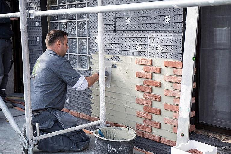 Het metselwerk wordt in de vorm van steenstrips verlijmd aan de betonnen elementen.